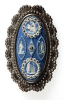 Oval dark blue jasper cameo with white relief design, set in cut steel as a buckle. cut steel is multi faceted to imitate gemstones and is probably by Matthew Boulton. Some of the reliefs feature Aurora in her chariot and various muses and sacrifices.