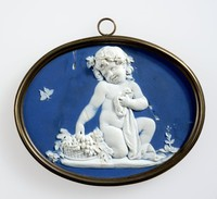 Horizontal oval dark blue jasper medallion with white relief figure of a child sitting by a basket of fruit, set in brass frame with ring