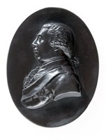 Oval black basalt medallion with relief portrait of George III (1738-1820) facing left, George III was King of Great Britain and Ireland, Baptized George Frederick William, Son of Frederick, Prince of Wales, who died in 1751 and Princess Augusta of Saxe-Gotha. He was unable to read English until the age of eleven but when his accession took place in 1760 he at once made a favourable impression as an English-born prince. In July 1761, his forthcoming marriage to Princess Charlotte of Mecklenberg-Strelitz was announced and their coronation took plate later that year. His political influence did much to create the circumstances which culminated in the American War of Independence. In 1788 the first signs of a mental aberration from which he was later to suffer became apparent. In 1809 his health broke down irretrievably, so his eldest son (later George IV) became Prince Regent in 1810. George III did not recover his faculties and died in 1820 after surviving several assassination attempts.
