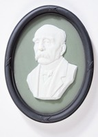 Oval tri-color jasper (green, black, and white) medallion with white relief portrait of Clemenceau, with black relief laurel leaf self-frame