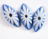 Three pointed oval or eye-shaped dark blue jasper buttons with white relief petals radiating from hole