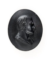 Oval black basalt medallion with relief profile portrait of Asclepiades facing right