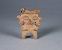 Standing figure with oblong, oversized head, raised oval eyes, ear spools, arms folded