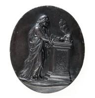 Oval black basalt medallion with relief scene of Sacrifice