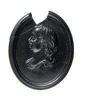 Oval black basalt medallion with relief profile portrait of King William III facing left, broken and repaired with large piece missing at top