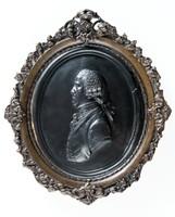 Oval portrait medallion of black basalt depicting Josiah Wedgwood (1730-1795) facing left in decorative metal frame.