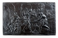 Rectangular basalt plaque of Venus at the forge of Vulcan. The plaque depicts Venus and Cupid visiting the forge to ask Vulcan to make arms for her son Aeneas. The relief shows Venus and Cupid waiting by a chariot as Vulcan and three other men hammer and forge a shield. With a chessplate in the foreground and a fire to the far right with arches and towers as a background.