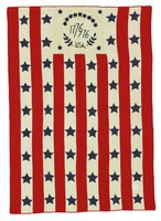 """Quilt has stars and stripes with the dates """"1776-1976"""" (commemorating the Bicentennial) emblazoned on the top."""