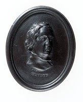 Oval black basalt medallion with relief portrait of John Dryden (1631-1700) facing right. John Dryden was born in Aldwincle near Thrapston in Northamptonshire the eldest of fourteen children. In 1650 Dryden went to Trinity College, Cambridge, where he studied the standard curriculum of classics, rhetoric, and mathematics. He graduated in 1654 with his BA, graduating top of the list for Trinity that year. Dryden returned to London during the Protectorate, where he obtained work with Cromwell's secretary of state, John Thurloe. This later helped him publish his first poem, Heroic Stanzas (1658), a eulogy on Cromwell's death which is cautious and prudent in its emotional display.