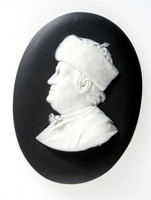 Oval black jasper medallion with relief white profile portrait of Benjamin Franklin (1706-1790) facing left, wearing a fur hat. Taken from a terra cotta portrait by John Baptiste Nini.