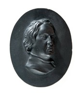 Oval black basalt medallion with relief portrait of John Dryden (1631-1700) facing right. John Dryden was born in Aldwincle near Thrapston in Northamptonshire the eldest of fourteen children. In 1650 Dryden went to Trinity College, Cambridge.where he studied the standard curriculum of classics, rhetoric, and mathematics. He graduated in 1654 with his BA, graduating top of the list for Trinity that year. Dryden returned to London during the Protectorate, where he obtained work with Cromwell's secretary of state, John Thurloe. This later helped him publish his first poem, Heroic Stanzas (1658), a eulogy on Cromwell's death which is cautious and prudent in its emotional display.