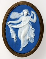 Oval dark blue jasper medallion with white relief figure of Zephyr, set in a chased brass frame possibly for insetting into furniture.