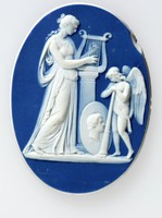 Oval dark blue medallion with white relief scene, depicting the classical subject of a muse and a genius. The robed muse facing right playing a lyre that is mounted on a pedestal. A shield with profile portrait rests at the base, in front of a winged figure playing a trumpet.