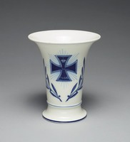 Small trumpet vase of white hard-paste porcelain made to commemorate World War I, the front decorated in underglaze blue with the image of a radiant Iron Cross and the date 1914, the reverse with a small three-leaf oak branch and acorn below the date 1914-1916, with narrow blue bands below the lip, around the lower body, and at the foot.
