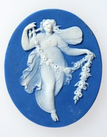 Oval dark blue cameo with white relief of Zephyr with a floral garland.