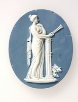 Oval blue jasper plaque with white relief of Euterpe, broken in several pieces. The modelling of Euterpe is attributed to John Flaxman Jr in around 1778. Wedgwood owned some muses figures which were created by Bouchardon from 1770. However it was not until 1777 that he decided to produce them so he requested Bentley to commission Flaxman to produce some more to complete the set.