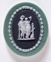 Oval tri-color jasper (green, black, and white) with white relief scene with man and woman decorated by Bert Bentley