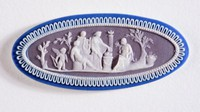 Oval tri-color jasper (dark blue, lilac, and white) cameo with white relief sacrificial scene with polished edges.