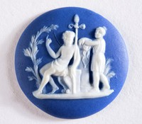 Round dark blue jasper cameo with white relief scene of two classical figures, one seated in front of tree with the other behind