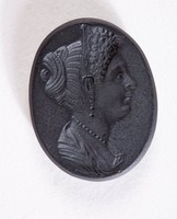 Small, oval intaglio of black basalt with the portrait of either Julia Augusta, daughter of Augustus, or Julia Flavia, daughter of Titus, to right, with elaborate hairstyle, drapery, and pearl necklace and earrings.