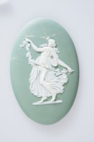 """Oval medallion of white jasper with green jasper dip and white relief decoration of a figure modified from the Dancing Hours series, also known as """"Floral Girl"""" holding a grape leaf vine with bunches of grapes."""