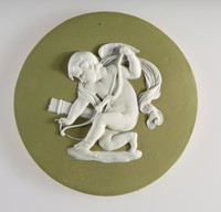 Round green jasper medallion with white relief of Cupid stringing his bow. Cupid also known as Eros or Amor, The god of Love, he is often seen portrayed with a bow and arrows in order to strike with his 'cupid's darts.