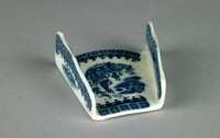 """Small asparagus shell of white soft-paste porcelain with low vertical, scalloped sides that taper towards one end, open at both ends to allow bundles of asparagus spears to be contained inside, the interior printed in underglaze blue in the """"Fisherman"""" or """"Pleasure Boat"""" pattern, above and below the printed scene a border of small blue square elements with a white dot in the middle above a repeating C-scroll and dot pattern, the exterior and interior sides with a similar repeating geometric pattern."""