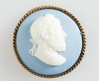 Round blue jasper cameo with white relief profile portrait of a man, in gold metal mount