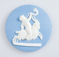 Round blue jasper plaque with white relief of boy blowing horn, riding on ram, possibly meant to represent saturn, broken and repaired