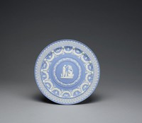 """Solid light blue jasper cabinet plate with white relief decoration, the outer edge with framed, stylized floral elements, the outer edge of the well with heavy garlands held by ram's head masks with banners on either side and extending below, between the garlands are small relief scenes of cupids and animals alternating with hanging trophies, the center with a band comprised of a ribbon encircling a leafy vine and this enclosing the scene """"Sacrifice to Concordia."""""""