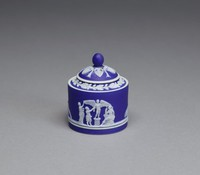 Miniature round covered container, or box, of white jasper with dark blue jasper dip, the body with small relief scenes in white including a group with a cage, a pair of lovebirds, and Cupid with outstretched wings on a pedestal, a recumbent sheep (possibly allegories of love and matrimony), the domed cover with an oak border and anthemion motifs radiating from the ball finial.