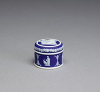 Miniature covered container, or box, of white jasper with dark blue jasper relief, the box with tiny relief scenes including, a classical group, Hebe and the Eagle, a pair of standing classical figures, and classical figures with a horse, on the cover the scene of Cupid as Oracle with a rose border around the edge.