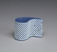 """Custard cup of """"tear"""" or """"comma"""" shape of solid dark blue jasper with white relief decoration in a lattice pattern."""