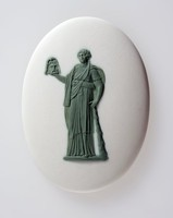 Oval white jasper medallion with green relief of Melpomene was one of the nine muses originally the goddess of music, song and dance before being named the muse of tragedy potrayed holding a tragic mask or sword often wearing a wreath of Ivy and wearing cothurnus boots.