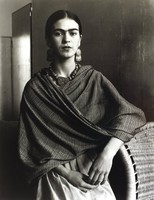 This black and white photograph shows a woman facing the camera. Her left elbow rests on a woven basket laying on its side, and she holds her hands together in front of her body with her fingers. She wears earrings, a necklace, a wrapped patterned shawl in a mid-tone, and a lighter dress or skirt. Behind her is a nondescript room.