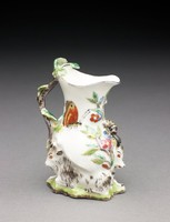 Small, delicate cream jug molded at the base with a pair of recumbent goats resting on a green and brown grassy ground and flanking a tree upon which rests a large black and yellow bumble bee, the pear-shaped body of the jug decorated in colorful enamels in shades of green, yellow, blue, brown, and black with leaves, flowers, and two large butterflies, the slender, curved handle disguised with brown and green enamel as a leafy branch with bocage leaves at the top, the lip of the jug rimmed with brown enamel.