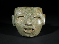 Carved stone mask with deep oval eyes, arched brows, broad nose, deeply carved, slightly open mouth. Ear flanges pierced.