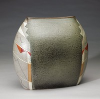Large, oblong vase of heavy, beige glazed stoneware, the sides are rounded and the opening at the top is narrow, each end of the vase is decorated in an abstract, semi-geometric pattern in shades of gray, white, rust, black, and beige, the central body is decorated on each side with a broad stripe of mottled, almost metallic, gray glaze.