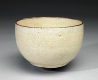 Small, round, footed bowl of reddish-brown colored stoneware and covered with a slightly imperfect, thick, creamy, pitted white glaze that reveals the clay beneath in an irregular manner at the rim and in the well.