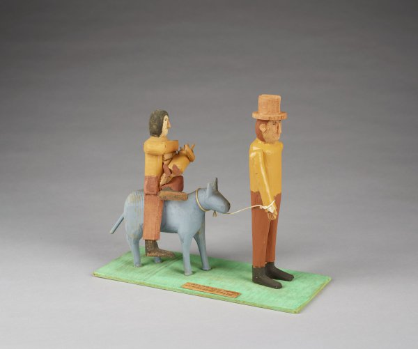 Joseph leads donkey on which Mary and Jesus are riding, figures wearing brown and tan, donkey blue/gray, ground green.