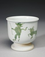 Small footed cup of creamy beige stoneware with a slightly flared rim, covered with a flecked opaque white glaze upon which are painted simple human and animal figures in greenish gray around the main body of the cup, the foot is unglazed.