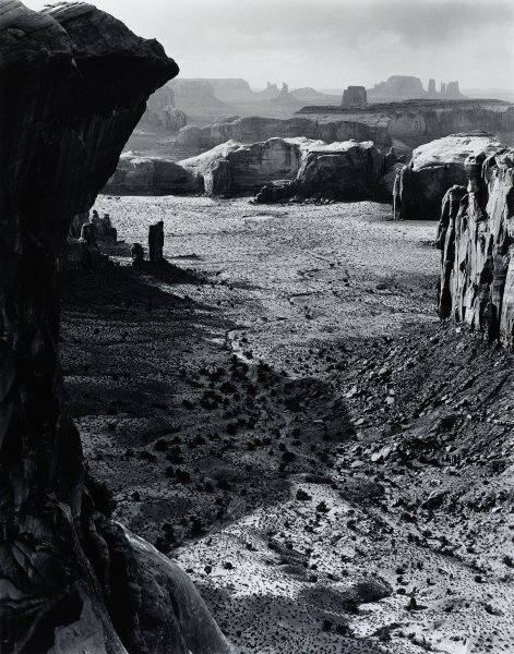This black and white photograph shows a valley in the desert between two rocky outcroppings framing the landcape at the left and right of the image. The landscape extends into the distance, showing a number of receding mesas.