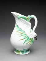 Large footed jug of earthenware covered with bright majolica glazes, the main body bulbous and covered with a thick, opaque white glaze, with an upward reaching, elongated spout, the sides molded to look like the outstretched wings of a swan, the handle in the form of a long, curving swan neck, the swan head with small eyes and slightly open black beak forms the terminal, the lower body, around the foot and lip of the jug with molded decoration in the form of water grasses in various shades of green and yellow.