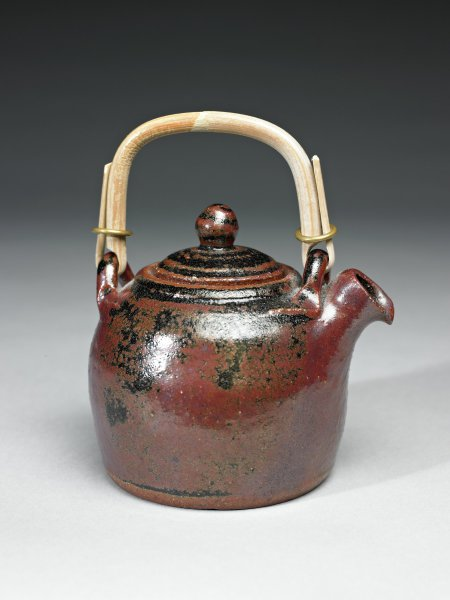 Small teapot of coarse red earthenware with a short, squat spout and a cover with a round finial, the bail handle made of bamboo attaches to two metal rings on either side of the upper teapot, the body is decorated with an ash glaze in a pattern of leaves and various splashes of colors in shades of white, black and red, the cover is decorated with a black spiral that extends around the cover and onto the finial.