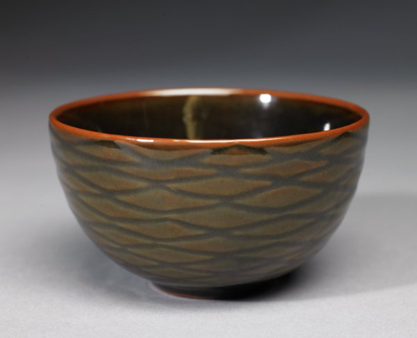 Small, deep bowl of grayish stoneware, with small foot, the body covered in a slightly mottled, gray-green glaze with a lattice or web-like design on the exterior, the thin glaze on the rim exposes the clay beneath.