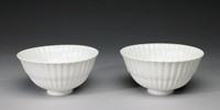 """Pair of white, footed, slightly flared bowls of hard-paste porcelain, the body molded into a fluted, or """"bamboo,"""" pattern that is in two sections, a smaller lower section and larger upper section."""