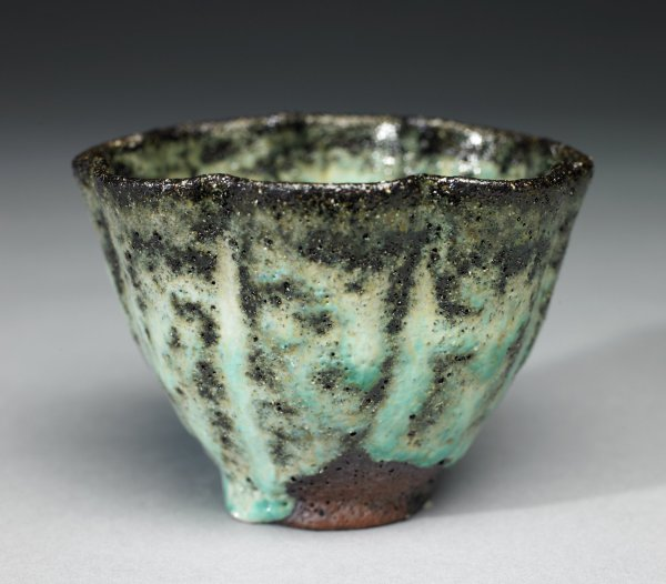 Small footed, irregularly round bowl of reddish earthenware covered with a greenish ash glaze, which is runny, drippy and scorched in spots, it runs irregularly down the sides of the bowl leaving part of the foot unglazed.