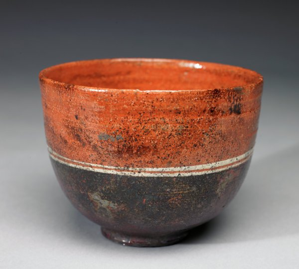 Small stoneware bowl with low foot and tall sides, Raku fired, the body glazed a bright reddish-orange and with two narrow cream-colored bands around the middle, the glaze with irregularities and dark scorch marks that cause the orange glaze of the lower body to be mostly obscured.