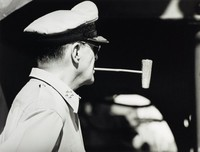 This black and white photograph represents a middle-aged man, Douglas MacArthur, standing just beyond profile facing away from the camera. He wears a cap and has five stars on the collar of his light-colored shirt. He holds a pipe in his mouth. The background is out of focus.