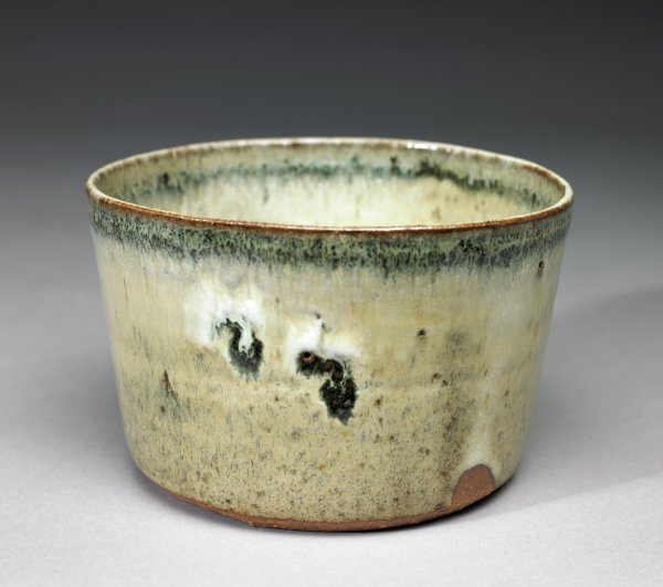 Small, irregularly round bowl of coarse reddish brown stoneware covered with an opaque glaze that is bluish at the rim and drips down white then becomes beige as the glaze runs down the body of the bowl, the glaze is speckled and flecked and the bowl is decorated on both sides with bluish squiggle patterns highlighted in white, there are glaze free spots at the foot where the potter held the piece while dipping it into the glaze.